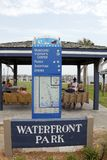 Waterfront Park Sign, Shelter and People. Southport, NC, USA - July 28, 2014: Waterfront Park sign below a Southport attractions map and guide. People near Stock Photography