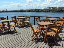 Waterfront patio deck. Tables and chairs on a restaurant patio or deck on a waterfront stock images