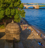 The waterfront Peter and Paul fortress at sunset. Embankment of the Peter and Paul Fortress in the rays of the sunset Royalty Free Stock Image
