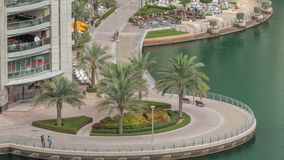 Waterfront promenade in Dubai Marina aerial timelapse. Dubai, United Arab Emirates. Waterfront promenade with palms in Dubai Marina aerial timelapse. Boats and stock footage