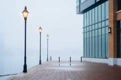 The Waterfront Promenade in fog and a modern building in Fells Point, Baltimore, Maryland.  royalty free stock photography