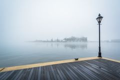 The Waterfront Promenade and fog over the harbor, in Fells Point, Baltimore, Maryland.  stock photos