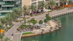 Waterfront promenade in Dubai Marina aerial timelapse. Dubai, United Arab Emirates. Waterfront promenade with restaurant in Dubai Marina aerial timelapse. Boats stock footage