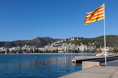Waterfront promenade in Roses, Spain. Waterfront promenade with a flag of Catalonia in Roses, Spain Royalty Free Stock Images