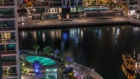 Waterfront promenade in Dubai Marina aerial night timelapse. Dubai, United Arab Emirates. Waterfront promenade with swimming pool in Dubai Marina aerial night stock footage