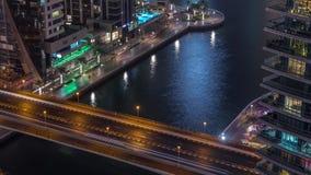 Waterfront promenade in Dubai Marina aerial night timelapse. Dubai, United Arab Emirates. Waterfront promenade with traffic on a bridge in Dubai Marina aerial stock video