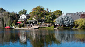 Waterfront property with doc and red canoe. And umbrella Royalty Free Stock Images