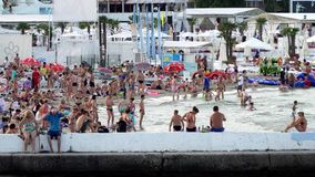 Waterfront resort. People sunbathing on the beach and swimming in the sea stock video