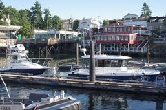 Waterfront at Friday Harbor, WA. Waterfront with restaurants and bars on San Juan island in Washington state with yachts docked at pier royalty free stock photos