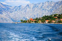 Waterfront of small town Dobrota along Bay of Kotor, Montenegro. View of coastal villas, gardens and mountains from sea. Mountain landscape. Summer travel and Royalty Free Stock Photos