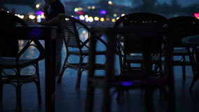 Waterfront tables. Empty waterfront tables at night with passing pedestrians and twinkling lights stock video footage