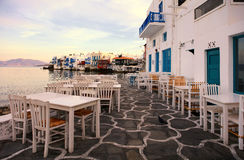 Waterfront tables, Mikonos Island, Greece. Empty table on patio outside restaurant on waterfront of Mikonos Island, Greece on sunny day stock image