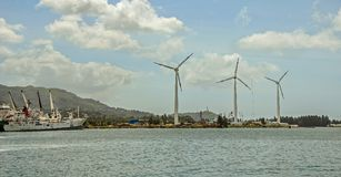 A waterfront with three wind turbines and a fishing ship near the green hills Stock Image
