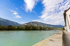 Waterfront view of Inn river along Inn promenade with mountain,. Waterfront view of Inn river along Inn promenade with big mountain, blue sky in background, in Royalty Free Stock Photos