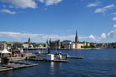 Waterfront view in Stockholm Sweden. Of a harbor facility with jetty and moored boats with historic buildings in the background on a sunny blue sky day Royalty Free Stock Image
