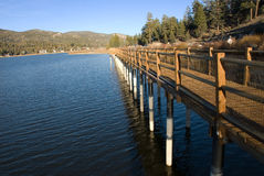 Waterfront walkway at Sunset. A very low sun casts beautiful deep yellow light on a waterfront walkway along Big Bear Lake Royalty Free Stock Images