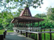Waterfront wooden pavilion. Background is green and the sky is clear Stock Photo