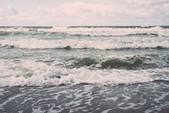 Watergolven die in zand meeslepen Stock Foto