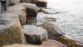 Watergolven tussen stenen op het overzeese strand stock videobeelden
