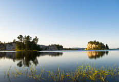 Watergrass. Cape Breton Bras d'Or Lake showing partially Submerged Grass in Foreground and Glassy Water and Tiny Islands in Background Stock Image