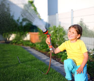 Watering. Little girl watering the grass in the garden Stock Photos