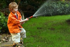 Watering. The little boy waters a garden from a hose Royalty Free Stock Images