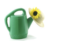 Watering Can. Green watering can and a straw hat Stock Images