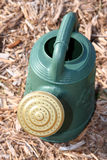Watering Can. Green watering can on mulch Stock Images