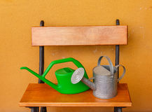 A watering can of  aluminium and a plastic one laid on wooden be. A corner of the terrace with  a wooden bench and a watering-can of aluminium  and a plastic one Stock Photography