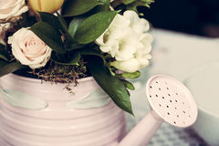 Watering can as flower pot. Selective focus on flowers and watering can royalty free stock photography