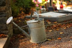 Watering can. Watering at the autumn cemetery royalty free stock images
