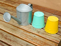 Watering can and buckets. Watering can, green and yellow metal buckets on table Stock Photo