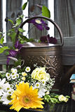 Watering can and cut flowers. Books and cut flowers with watering can Royalty Free Stock Images