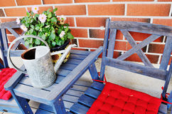 Watering can and flower pot on the table. Against brick wall Stock Images