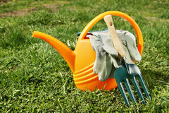 Watering can and gardening tools on the grass Royalty Free Stock Photo