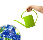 Watering can and globe Royalty Free Stock Photography