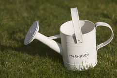Watering can on grass. Side view of watering can on grass with words my garden royalty free stock images