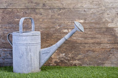 Watering can on grass against a wooden wall Royalty Free Stock Photo
