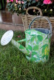 Watering can. Green watering can on field royalty free stock images