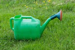 Watering can, on green nature grass background. Gardening Stock Images