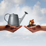 Watering Can Investing. Business concept as a two diverse human hands holding a water pot and an acorn seed in fertile soil as a financial metaphor for economic Stock Image