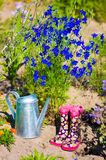 watering can and kids gardening boots in garden Royalty Free Stock Image