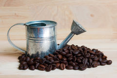 Watering Can miniature and Coffee beans Royalty Free Stock Images