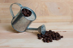 Watering Can miniature and Coffee beans Stock Photo