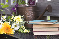 Watering can and old books. With a bouquet of flowerd Stock Images