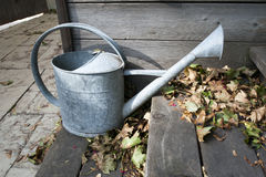 Watering can outside with dead leaves Royalty Free Stock Photography