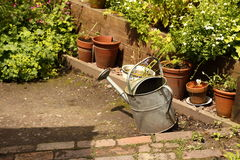 Watering can on patio A Royalty Free Stock Images