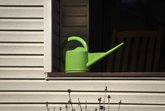 Watering Can on Railing. A green watering can on a railing with furniture in the shadow in background Royalty Free Stock Image