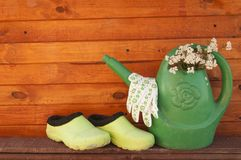 Watering can and rubber boots Stock Photography
