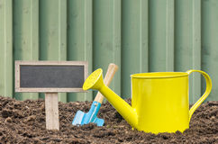 Watering can and shovel with a sign Stock Photography